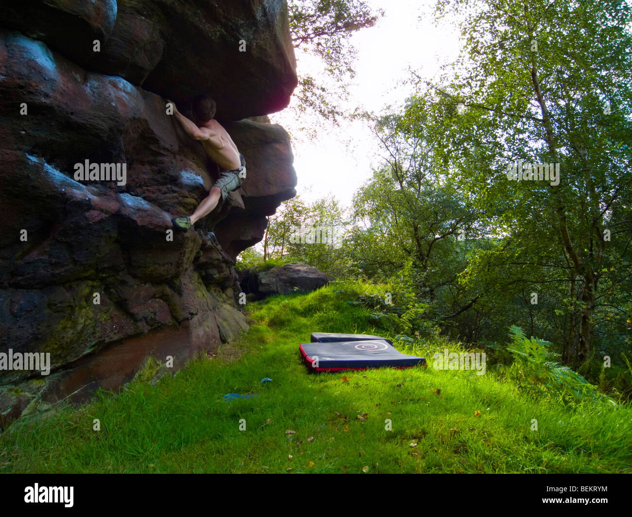 Climber doing a boulder problem in the Churnet Valley Staffordshire - Stock Image