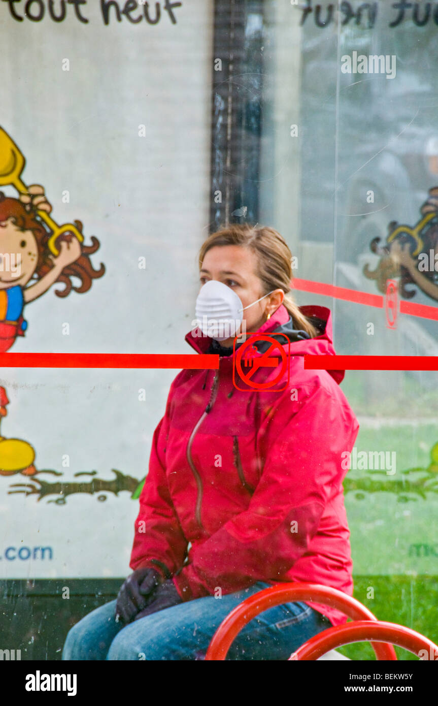Woman wearing a protective swine flu mask at bus stop - Stock Image