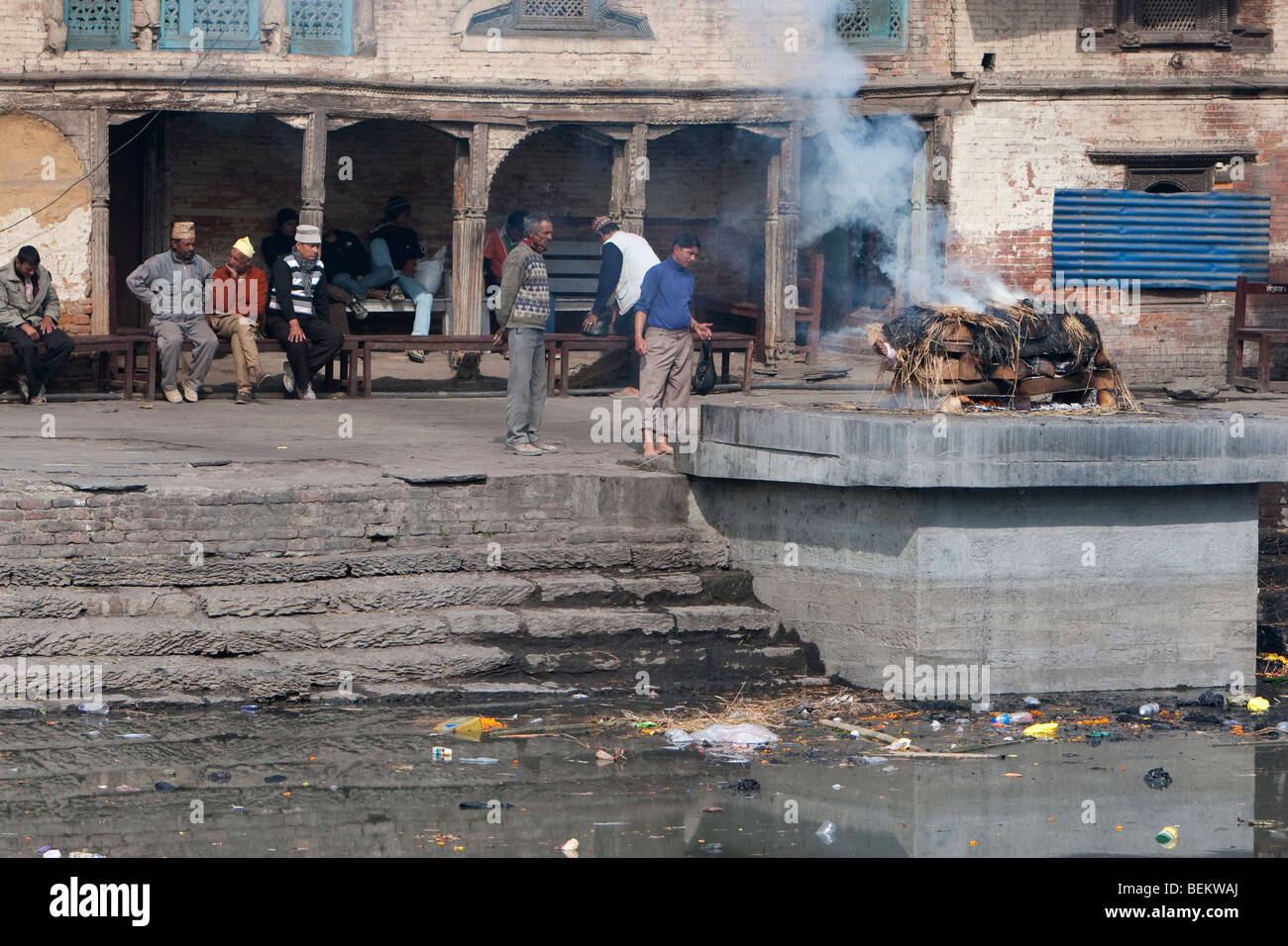 Pashupatinath, Nepal. A Family Member Oversees a Cremation on a Ghat on the Banks of the Bagmati River. - Stock Image