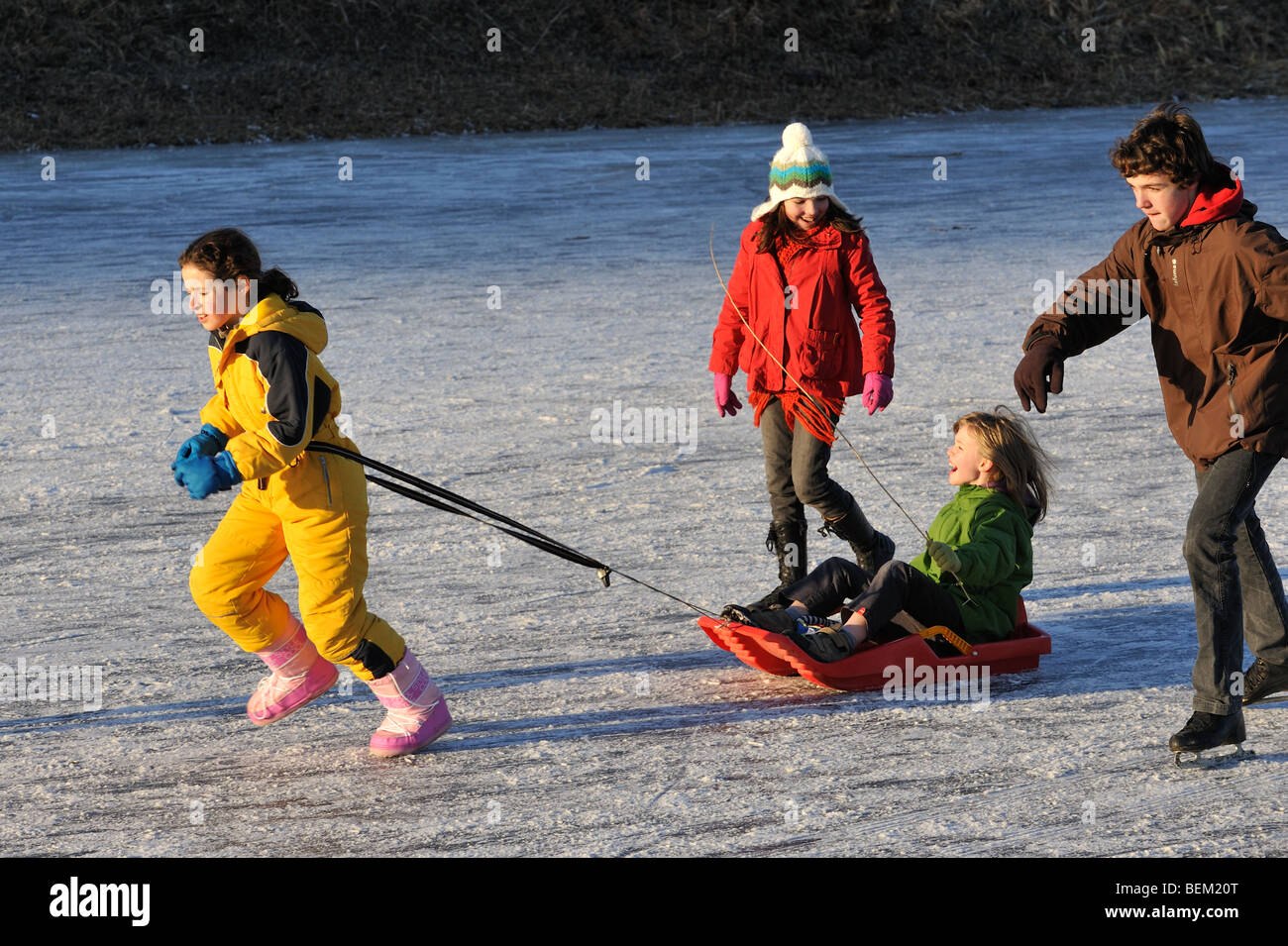 Child on sledge and ice skaters on frozen canal in winter - Stock Image