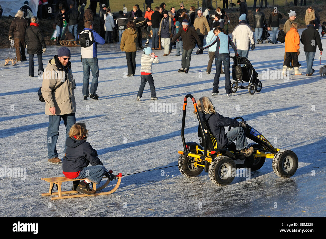 Child on sledge pulled by go-cart among ice skaters skating on ice of frozen river in winter - Stock Image