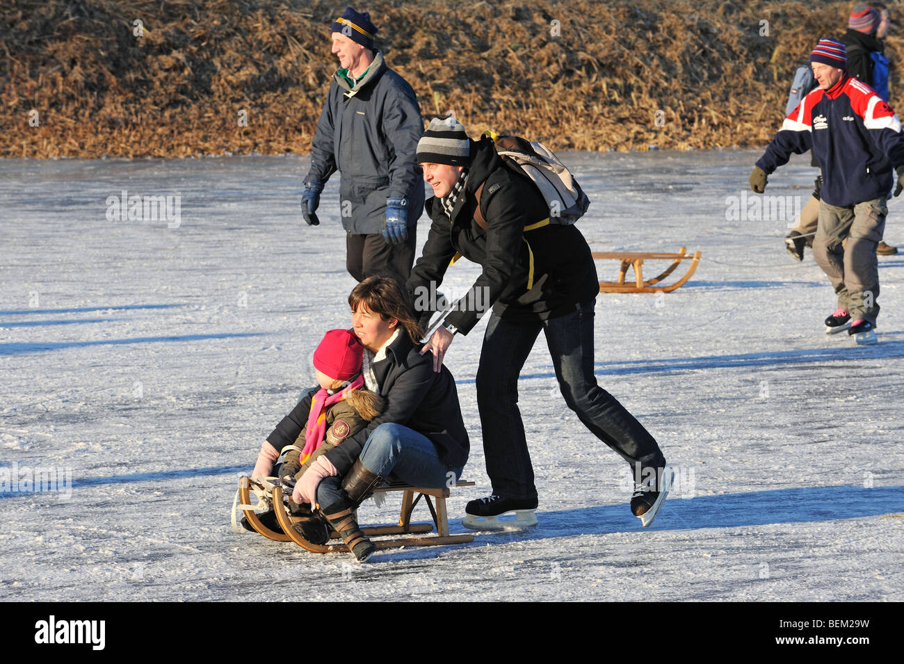 Mother and son on sledge pushed by father and ice skaters skating on frozen river in winter Stock Photo