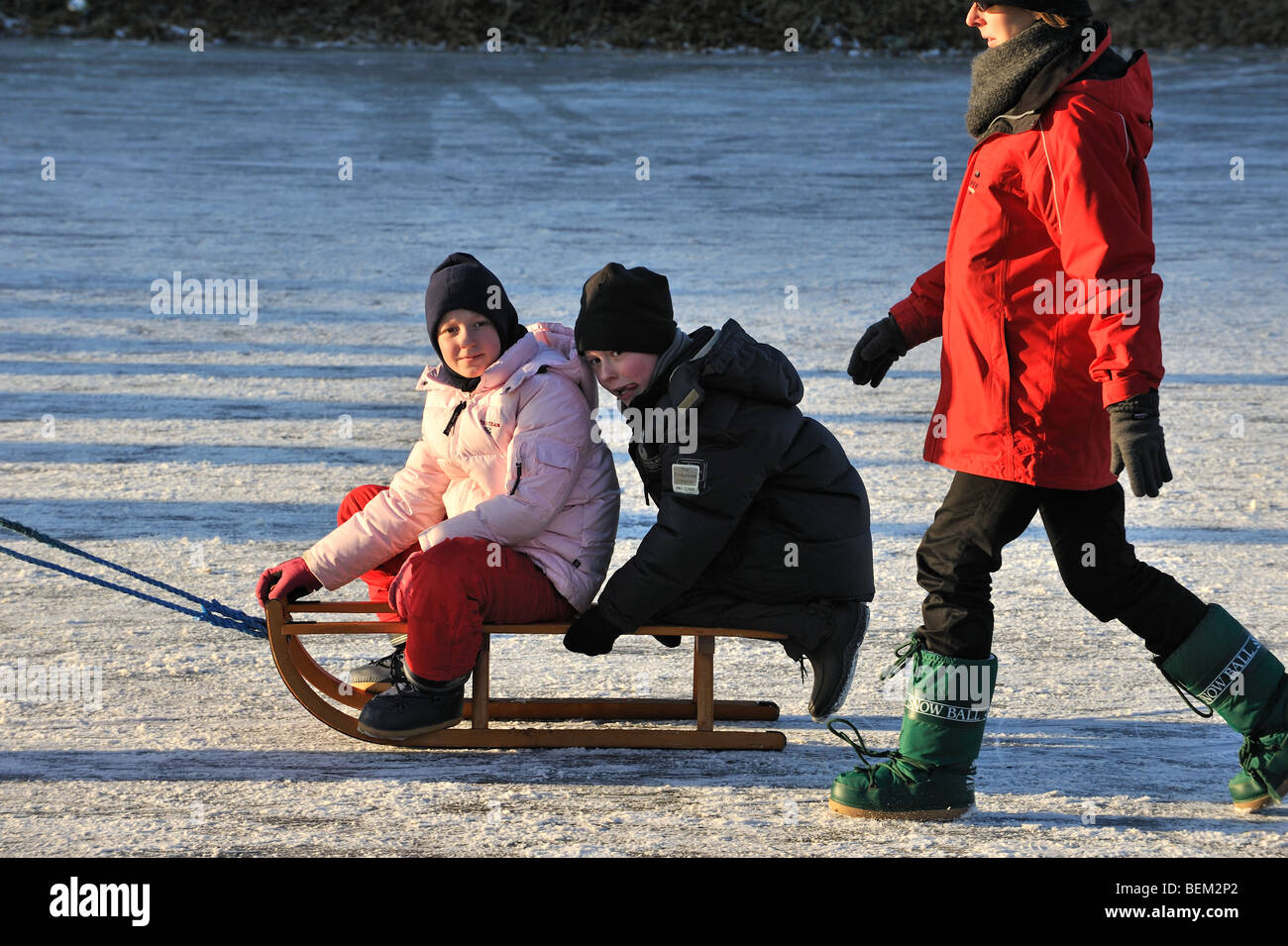 Children pulled on sledge and mother walking behind on ice of frozen river in winter - Stock Image