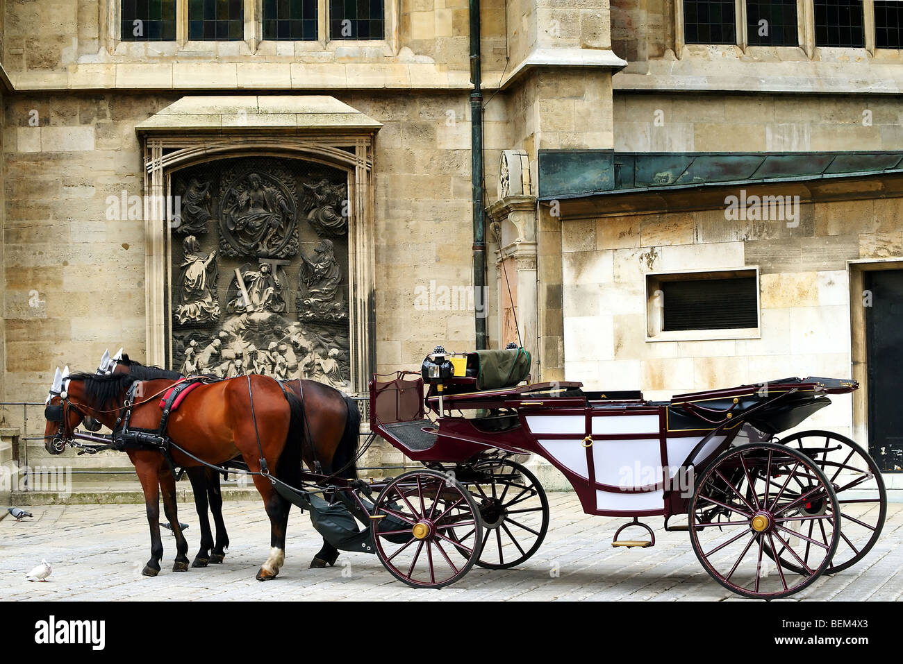 horses and coach on a street with old building in background - Stock Image