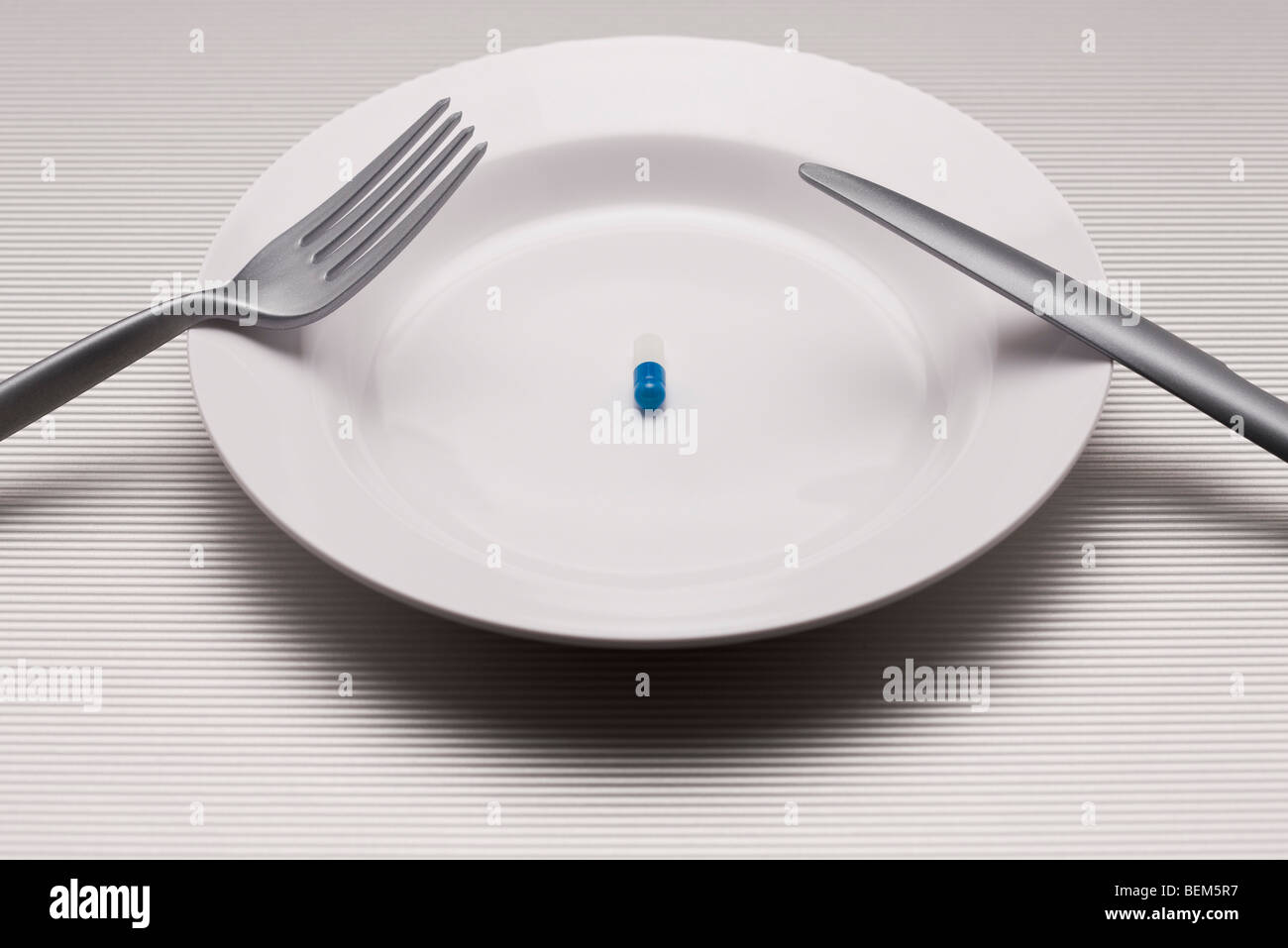 Food concept, single pill on plate - Stock Image