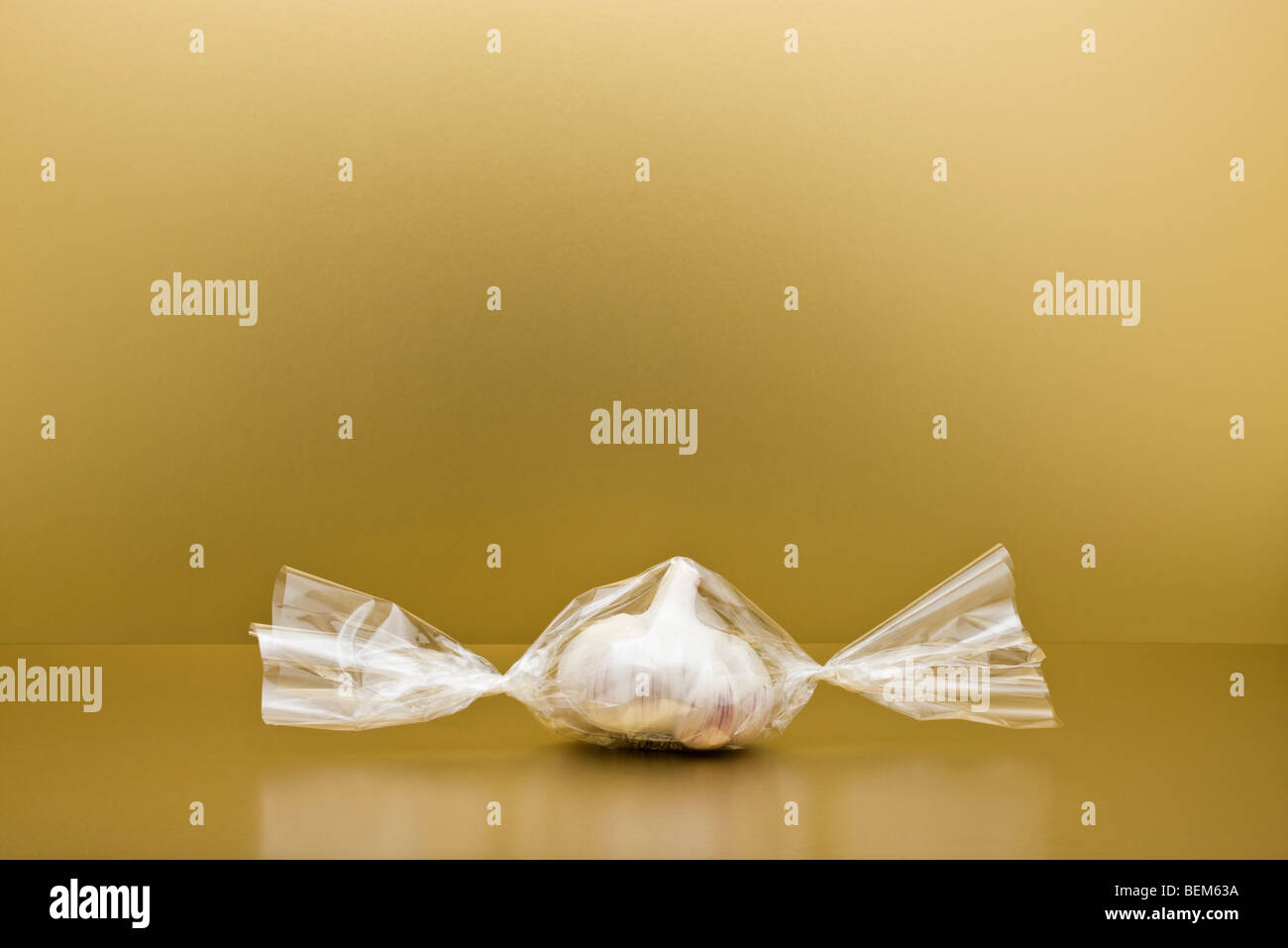 Food concept, head of garlic inside of cellophane candy wrapper - Stock Image