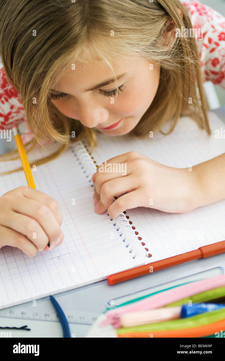 Girl writing in notebook, high angle view - Stock Image