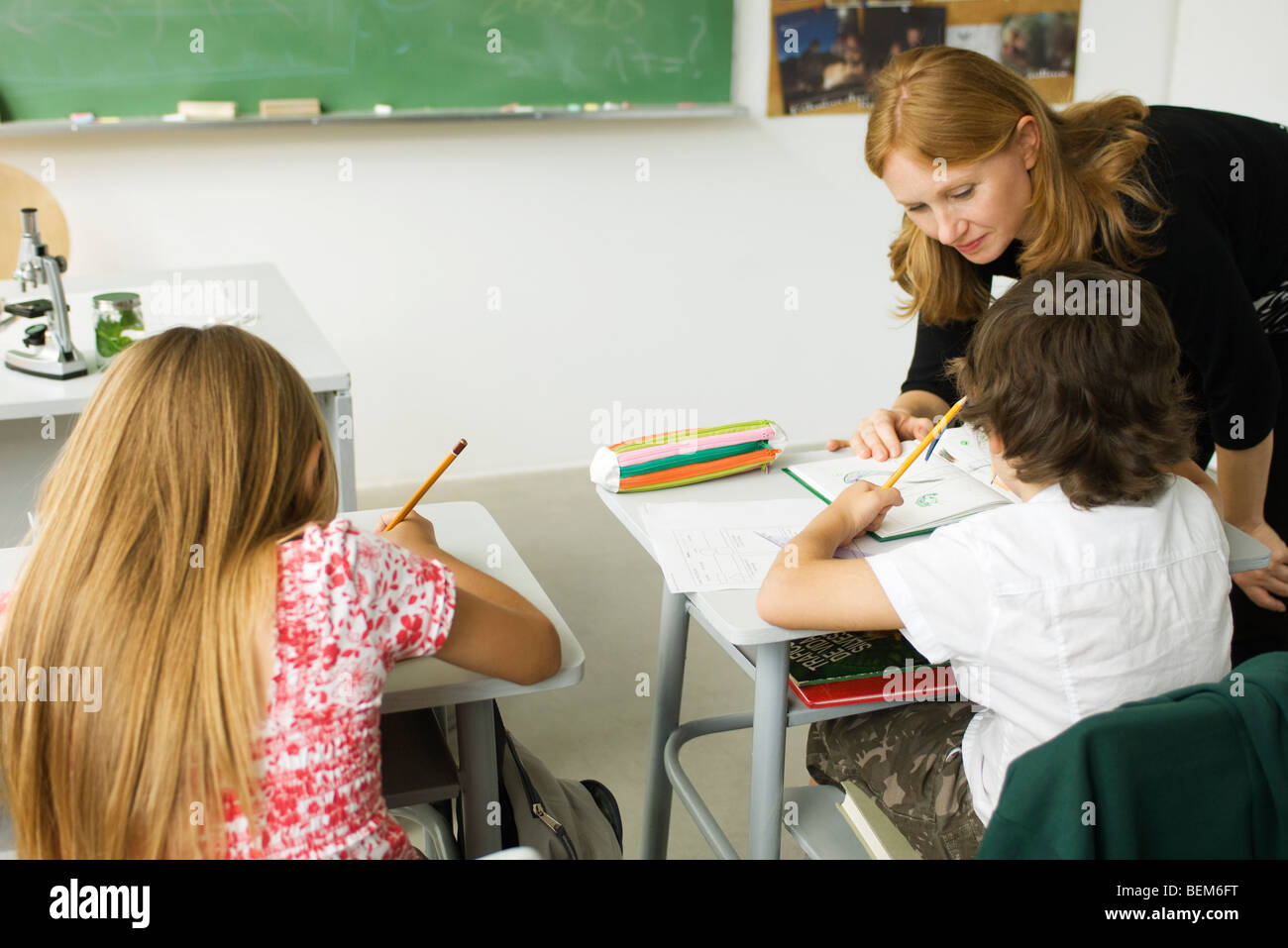 Elementary teacher leaning over student's desk, helping him with assignment - Stock Image
