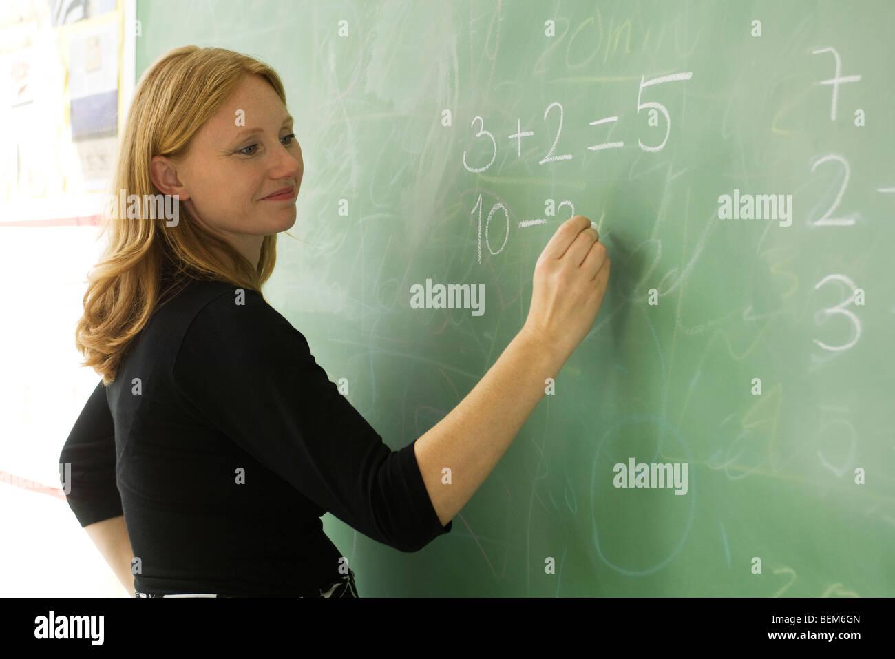 Elementary teacher writing math equations on blackboard - Stock Image