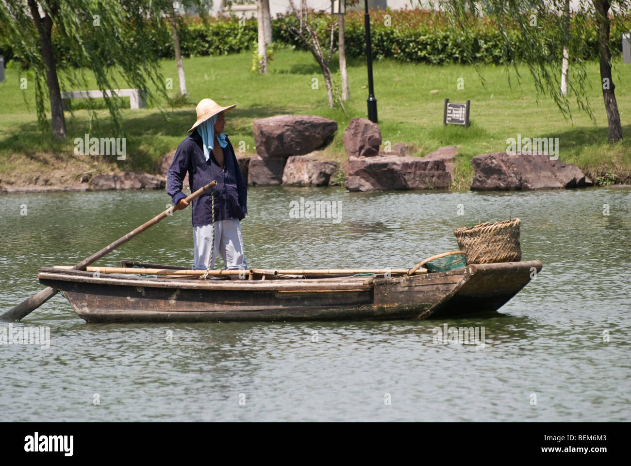 Man in a ancient wooden boat in a river of Xitang Xitang is an ancient scenic town in Jiashan County, Zhejiang Province, Stock Photo