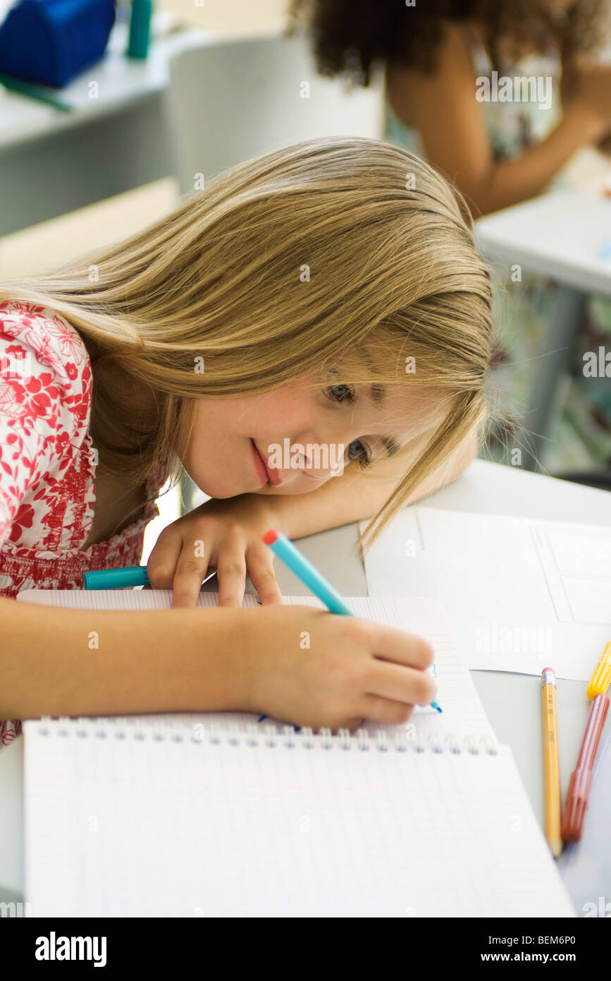 Girl resting head on arm, drawing in notebook - Stock Image