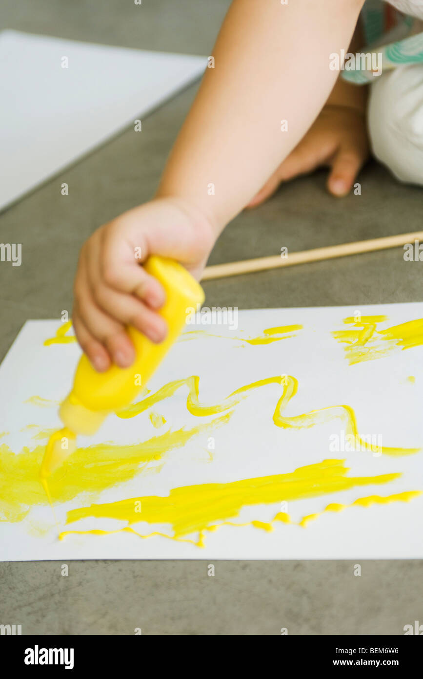 Child squeezing paint onto paper, cropped - Stock Image
