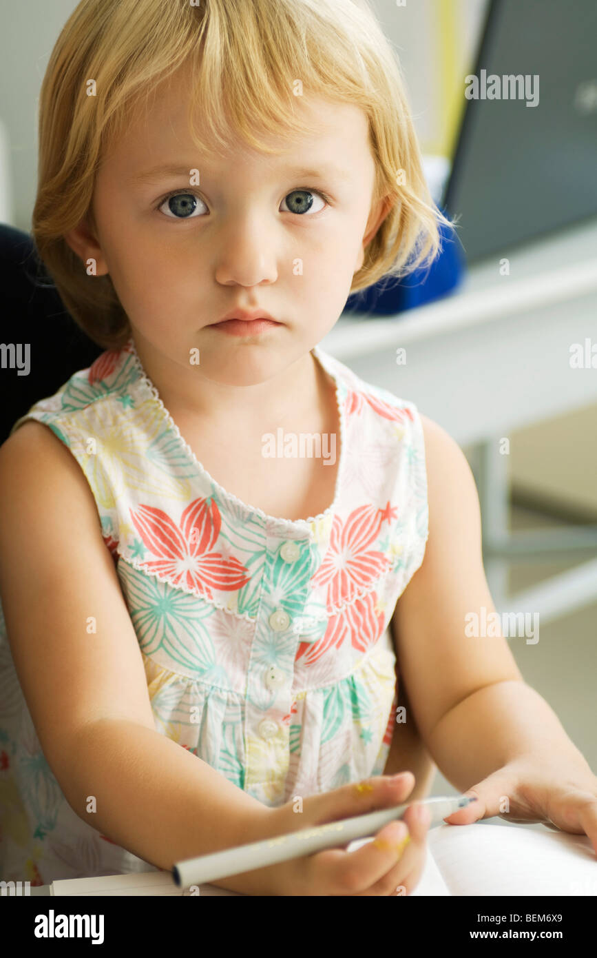 Little girl holding pen, looking at camera - Stock Image
