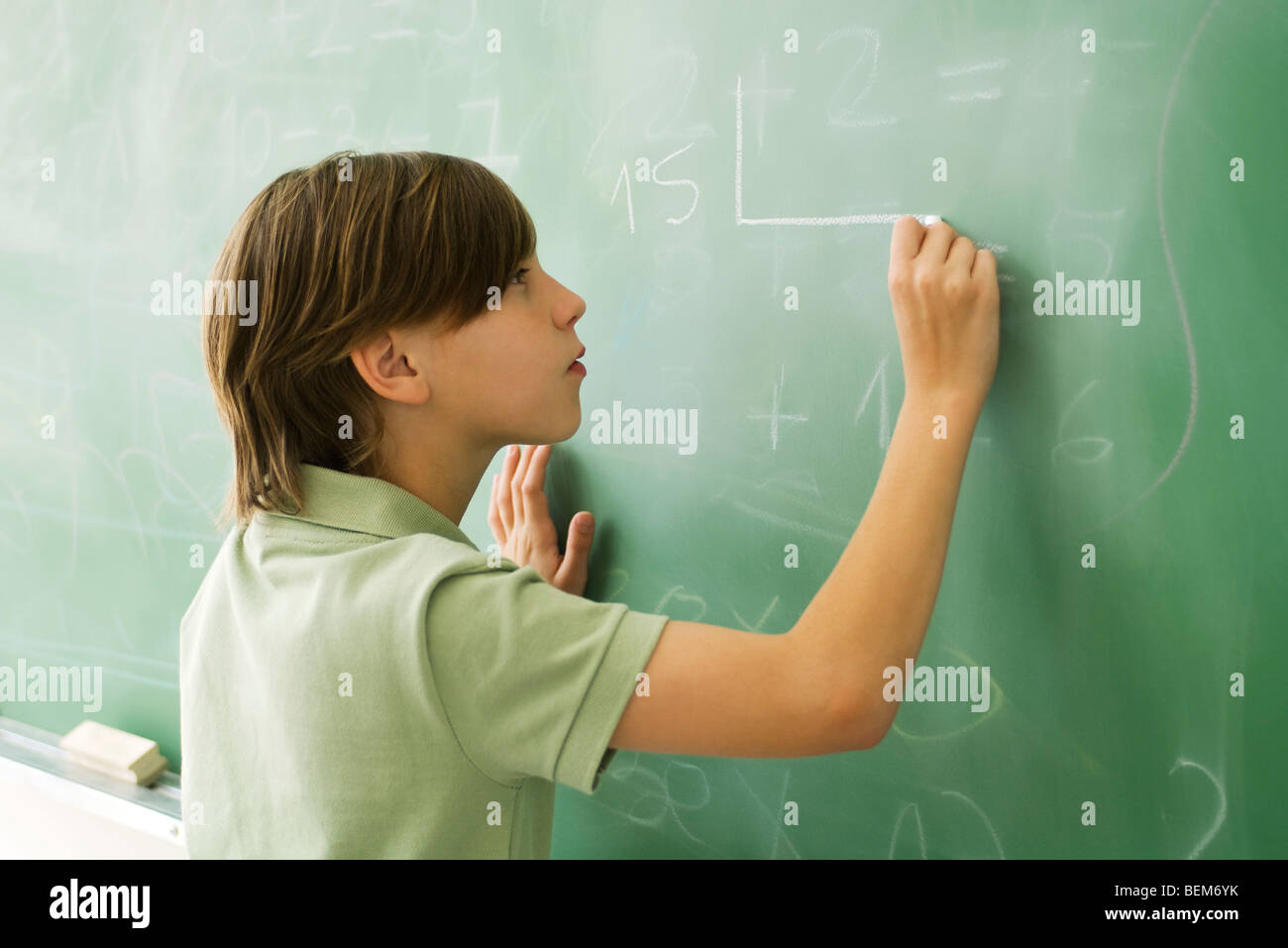 Boy writing on blackboard - Stock Image