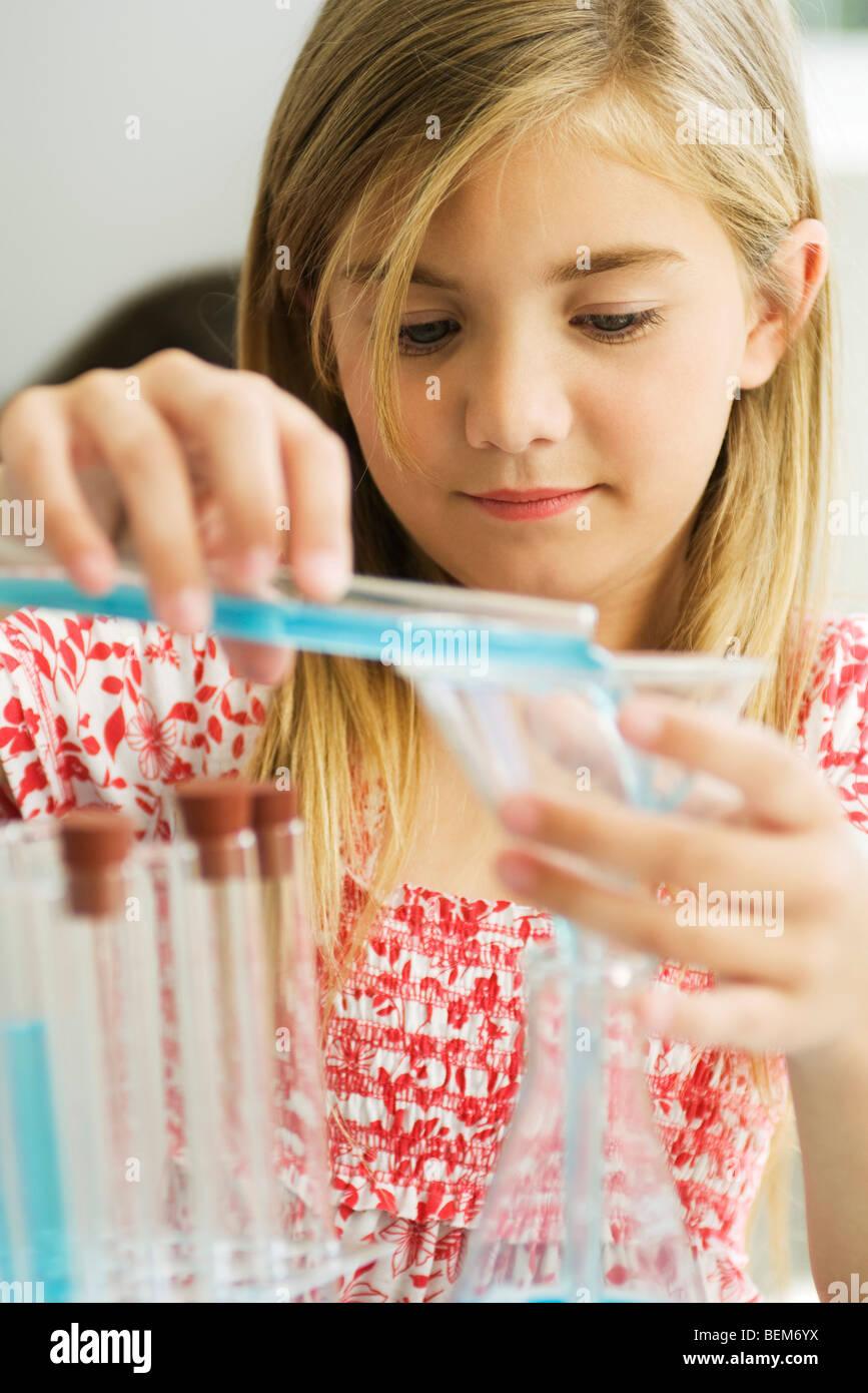 Girl transferring liquid from test tube to beaker - Stock Image