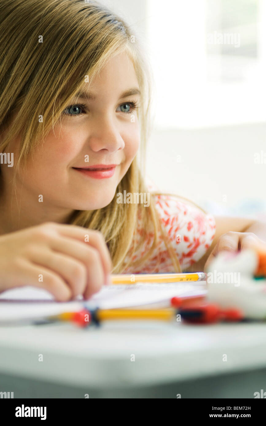 Girl daydreaming at school desk - Stock Image