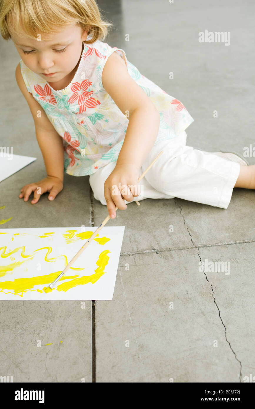 Little girl painting on paper - Stock Image