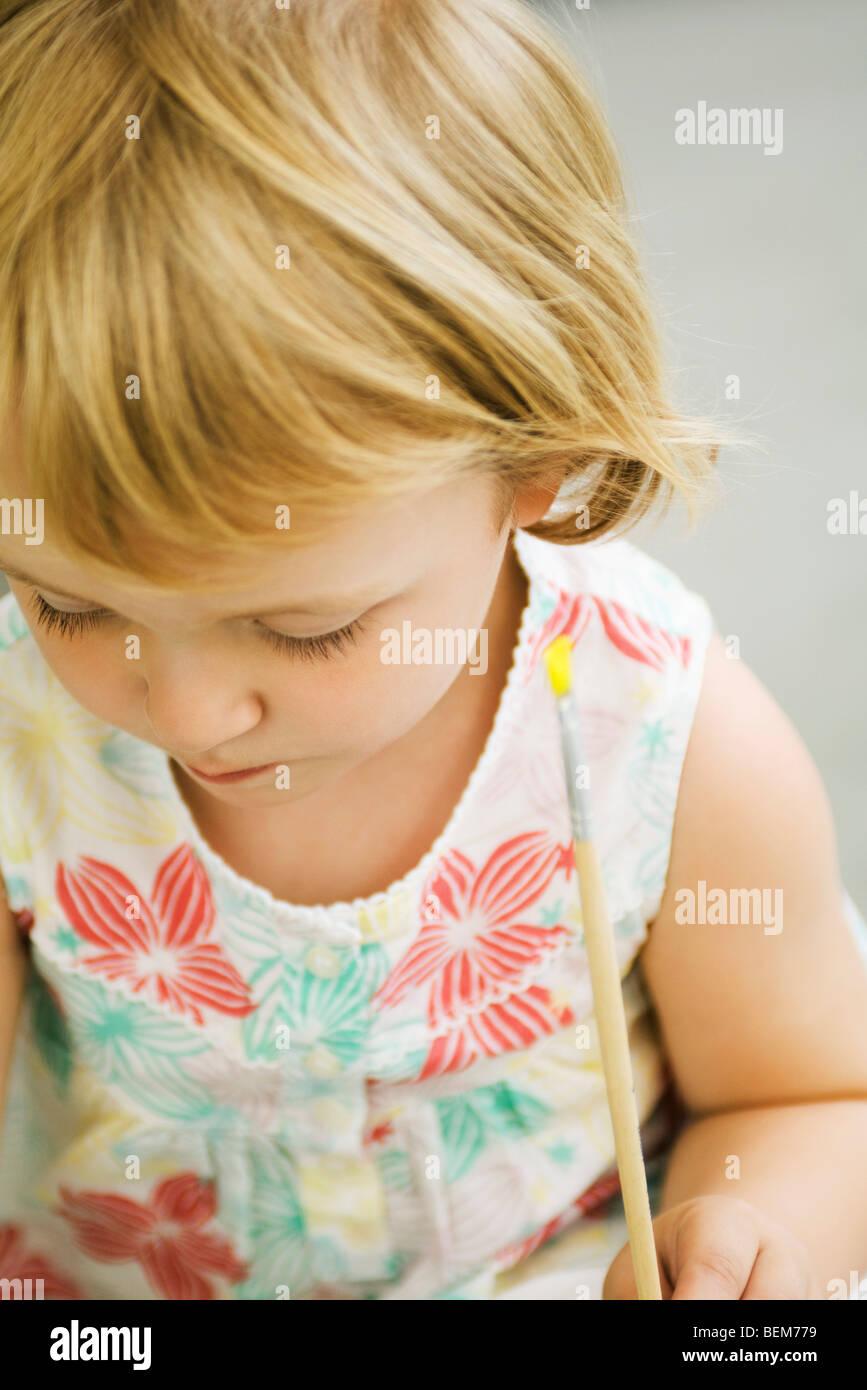 Toddler girl holding paintbrush, looking down - Stock Image