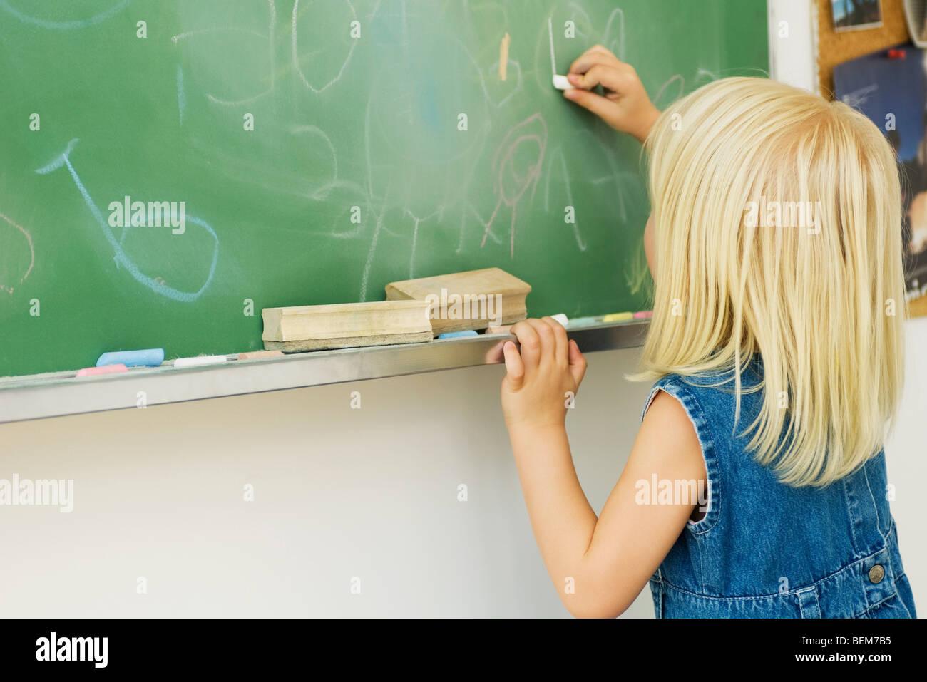 Little girl drawing on blackboard - Stock Image