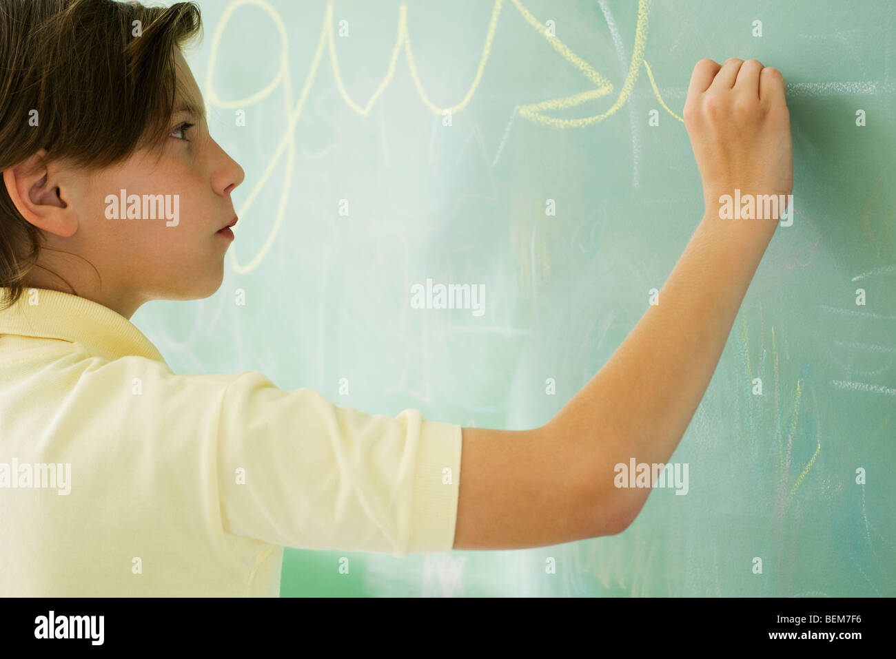 Boy writing in cursive on blackboard - Stock Image
