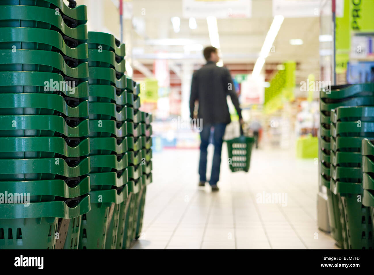 Shopping baskets stacked in rows, shopper in background - Stock Image