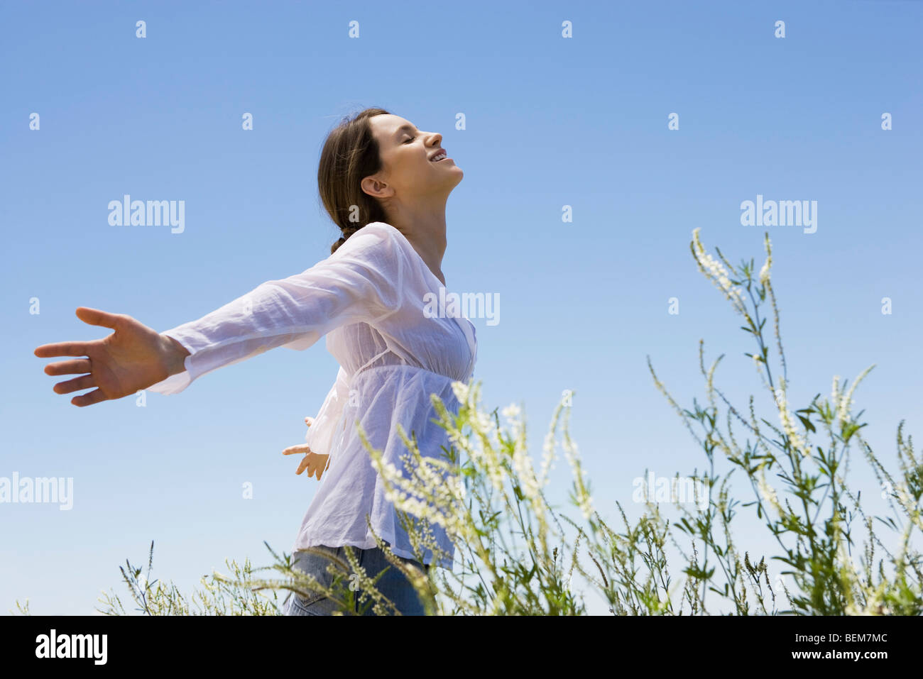 Young woman standing in tall grass with arms out, eyes closed - Stock Image