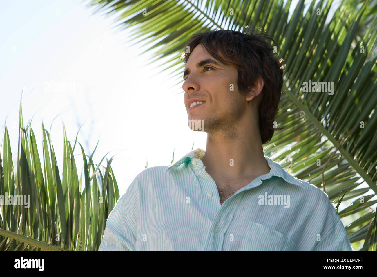 Man looking away, smiling, palm fronds in background - Stock Image