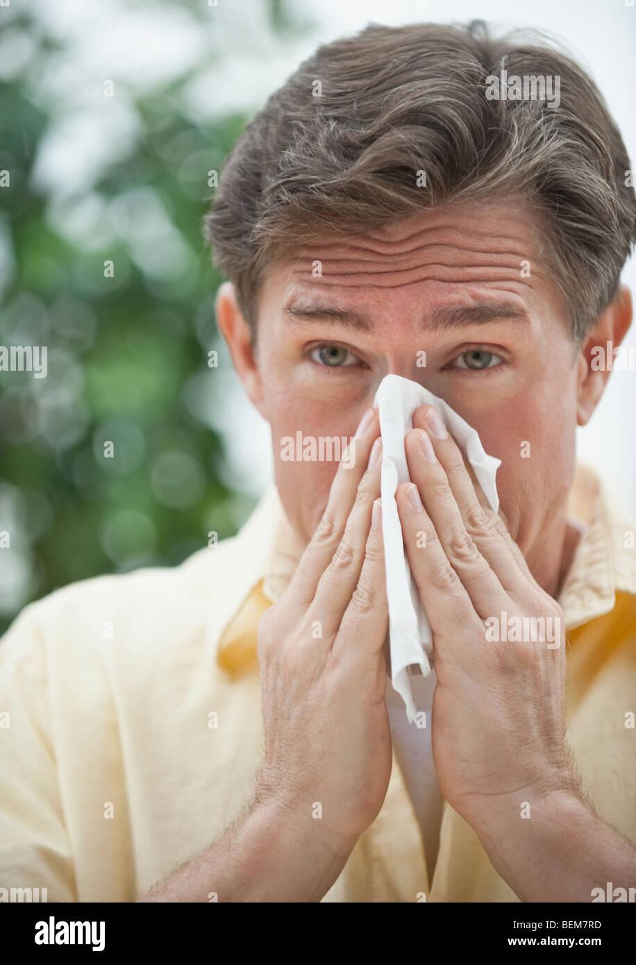 Man blowing nose - Stock Image