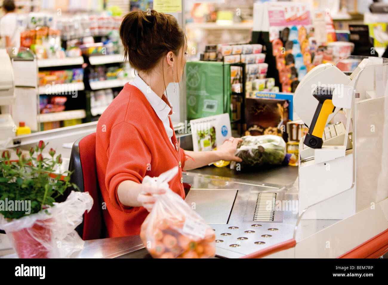 Cashier totaling grocery purchases - Stock Image