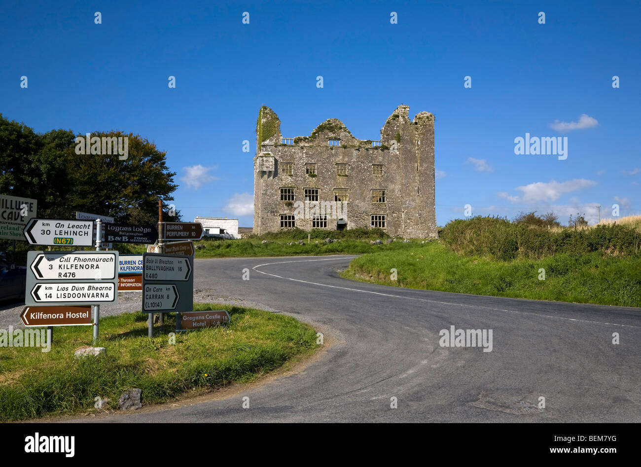 Road Signs by 15th Century Leamanagh Castle, The Burren, County Clare, Ireland - Stock Image