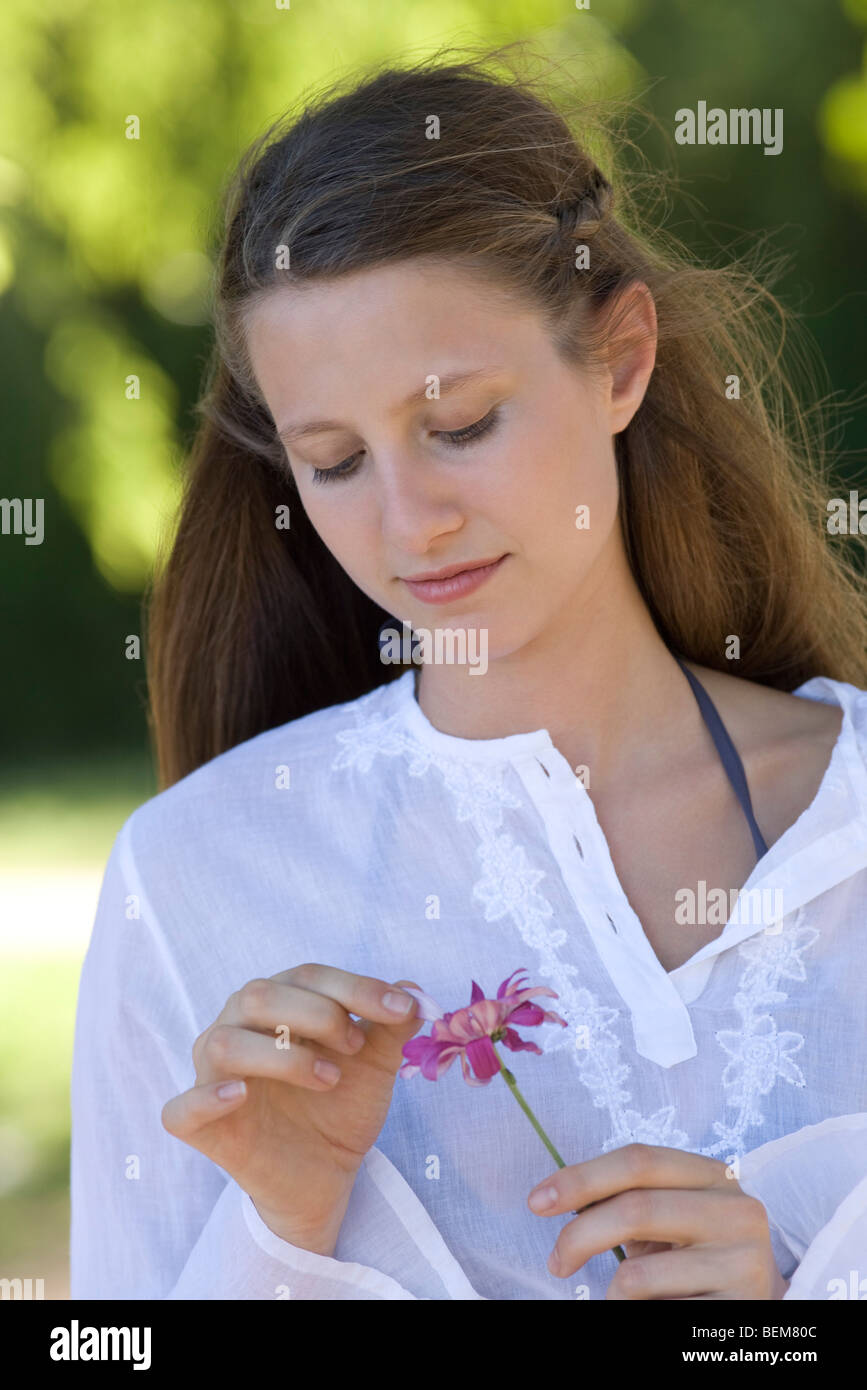 Young woman plucking petals from flower - Stock Image