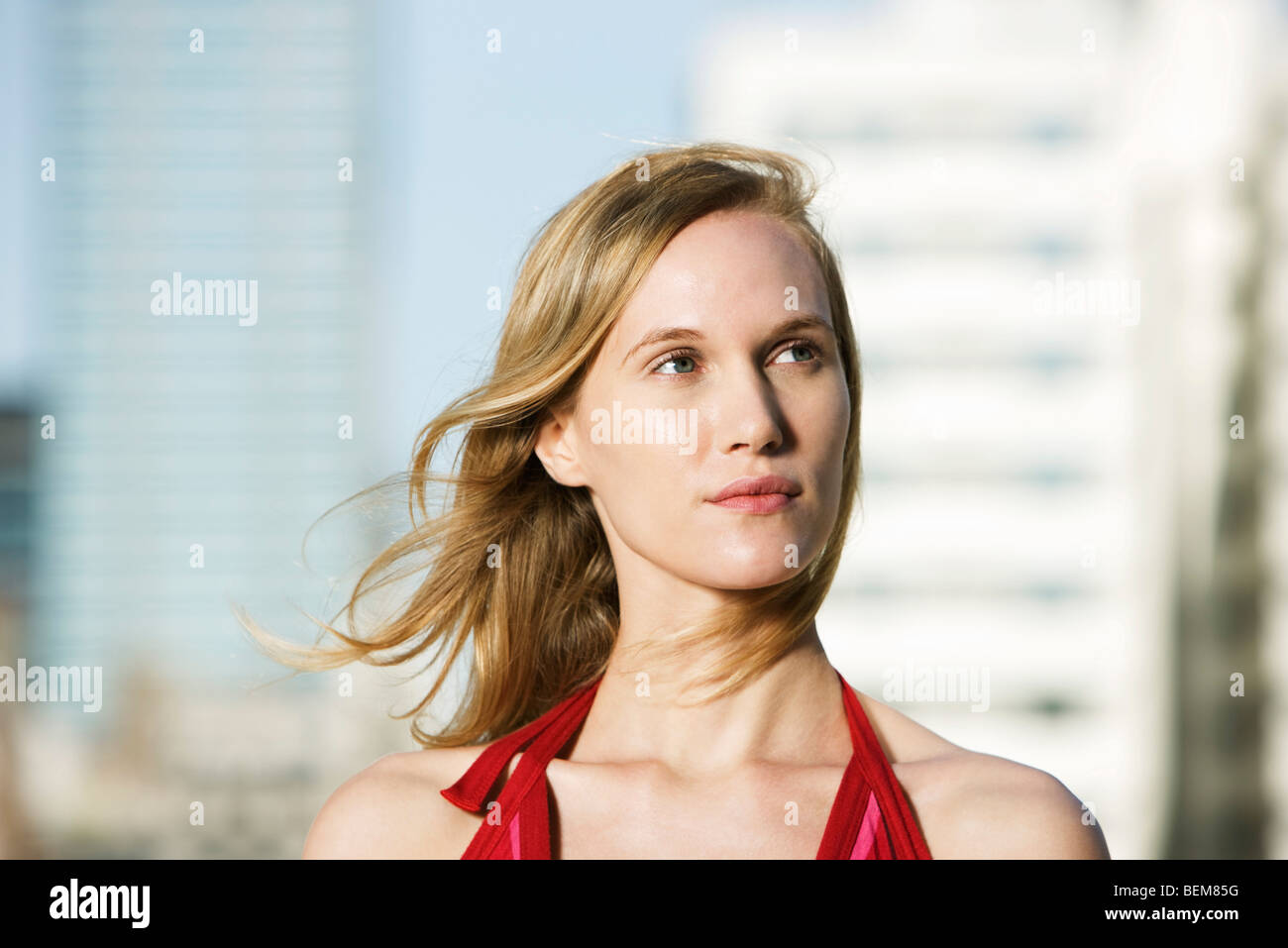 Young woman outdoors, looking away in thought, hair tousled by breeze - Stock Image