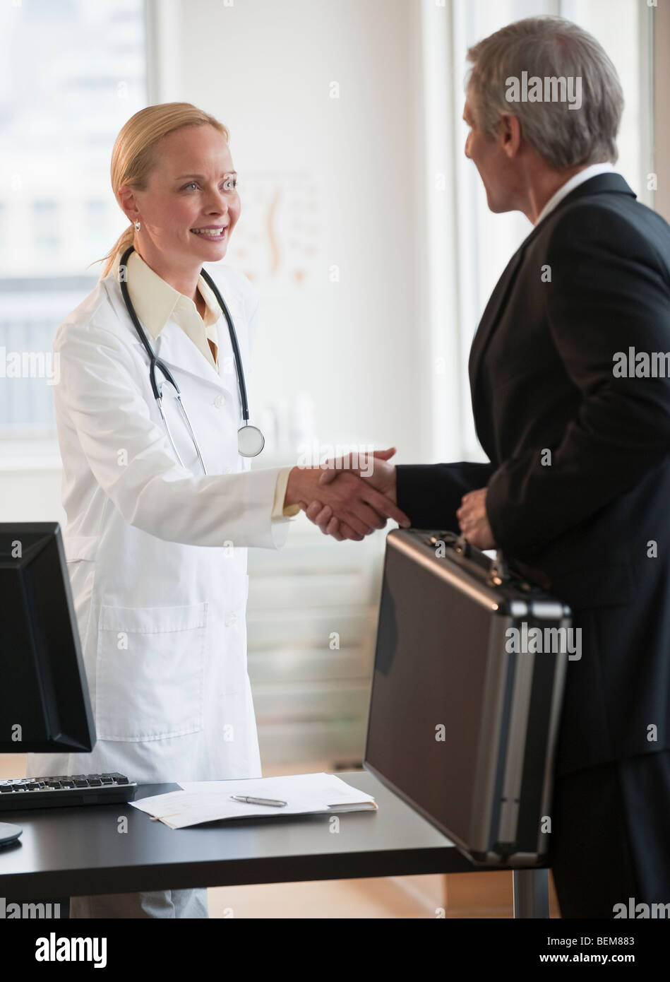 Female doctor greeting salesman - Stock Image