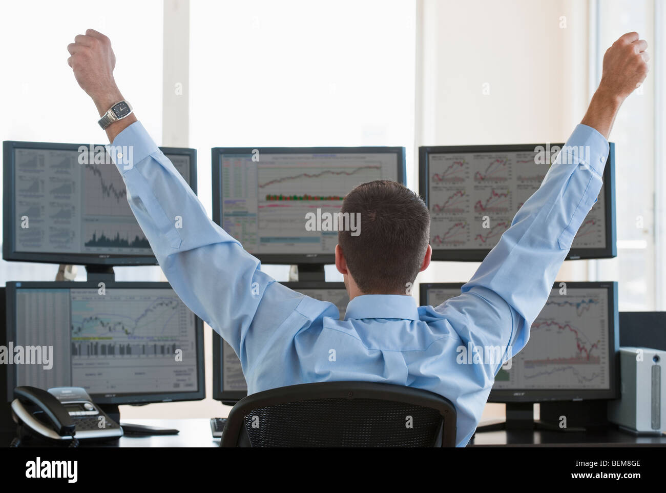 Male trader raising arms in success - Stock Image