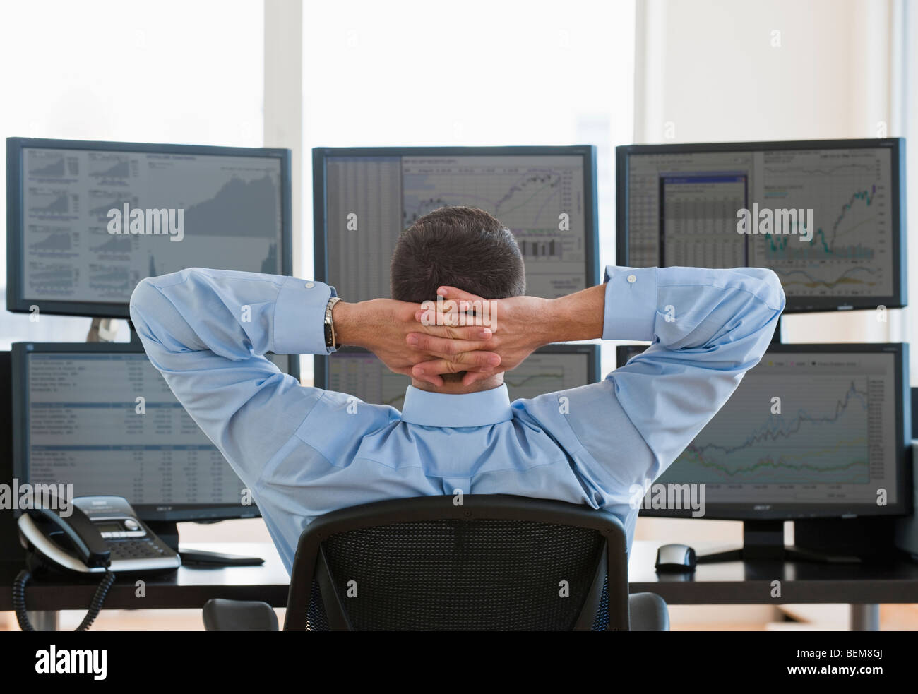 Relaxed male trader at work - Stock Image