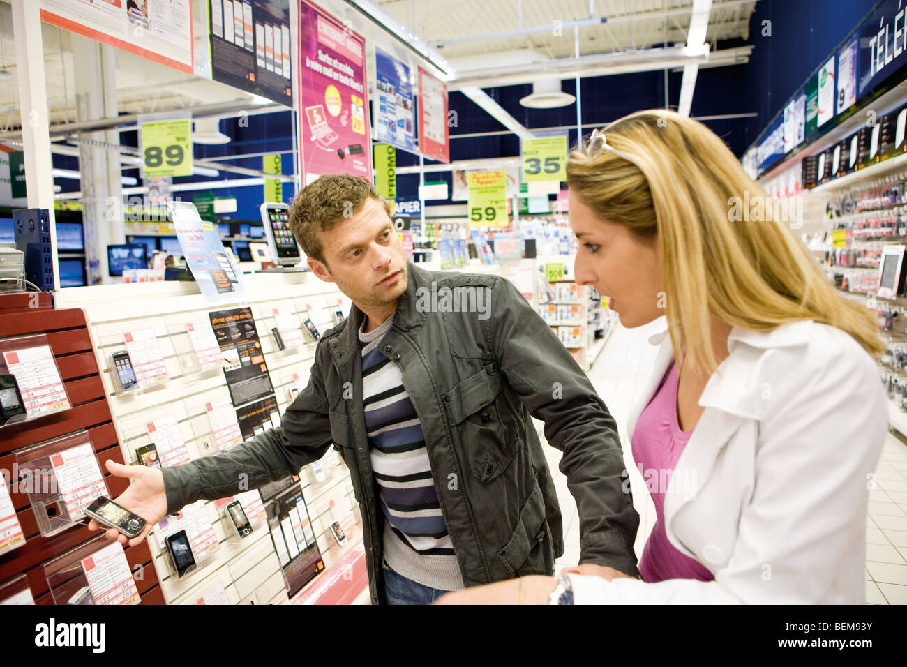 Couple looking at cell phones in electronics section of department store - Stock Image