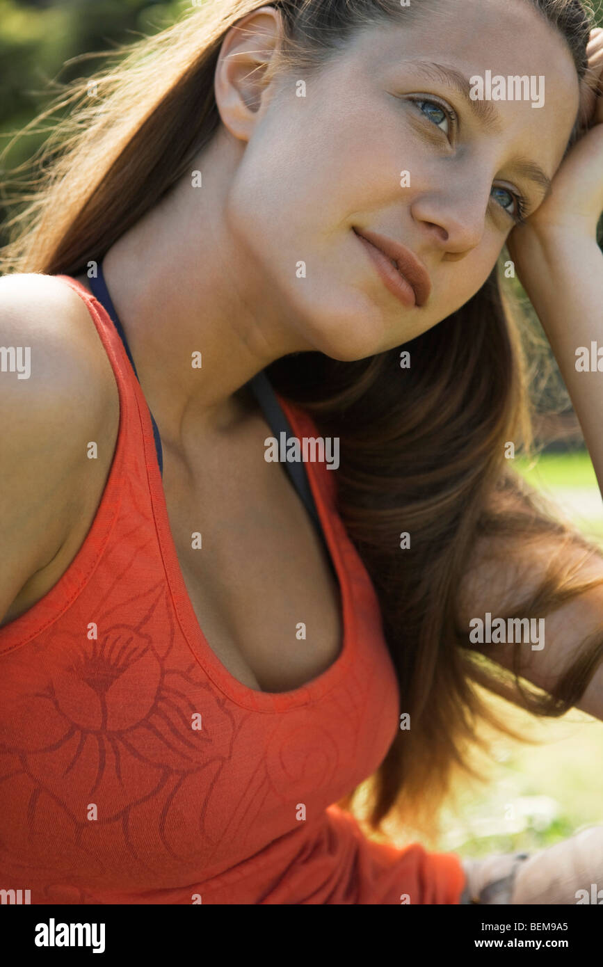 Young woman looking away dreamily, portrait - Stock Image