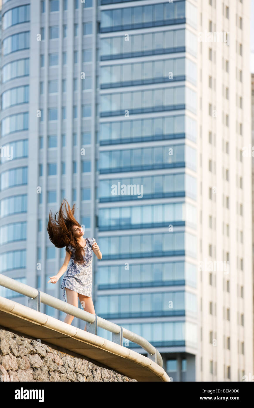 Young woman dancing on balcony, tossing hair - Stock Image