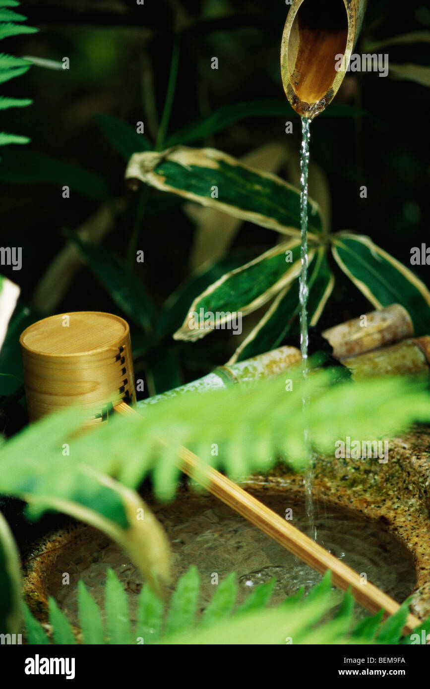 Water trickling from bamboo pipes into stone wash basin, Japan Stock Photo