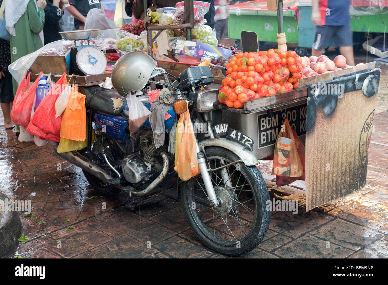 A motorcycle with a sidecar used as a fruit market stand in
