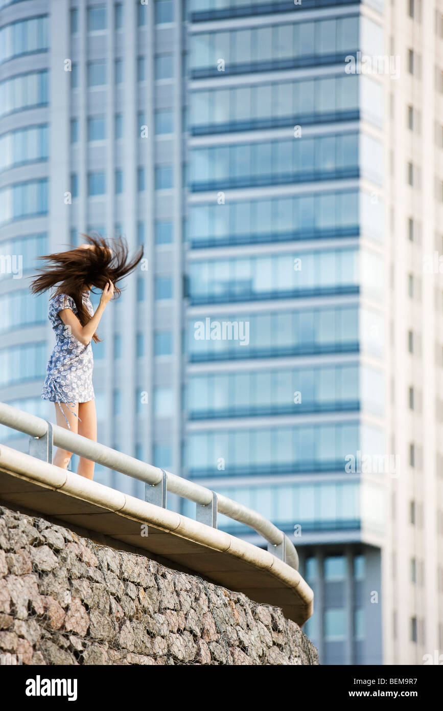 Young woman standing on balcony, tossing hair - Stock Image