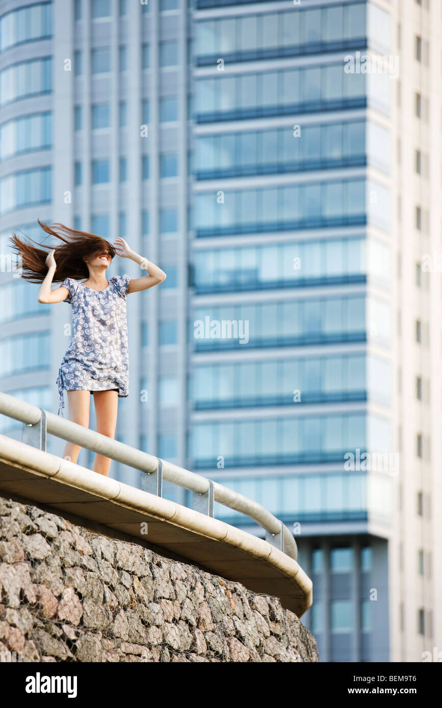 Young woman standing on balcony, wind blowing long hair across face - Stock Image