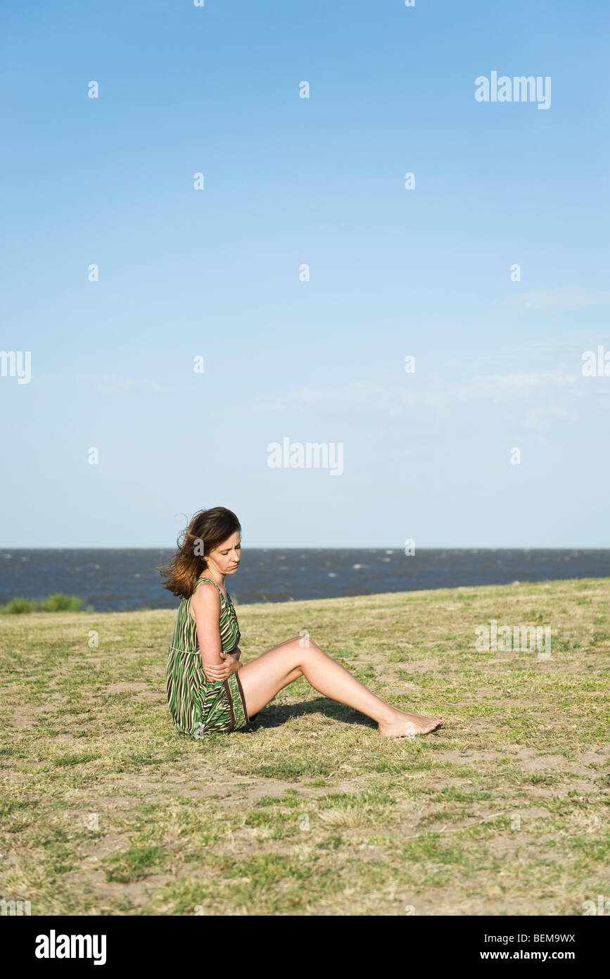 Woman sitting on grass with arms folded over stomach, head down - Stock Image