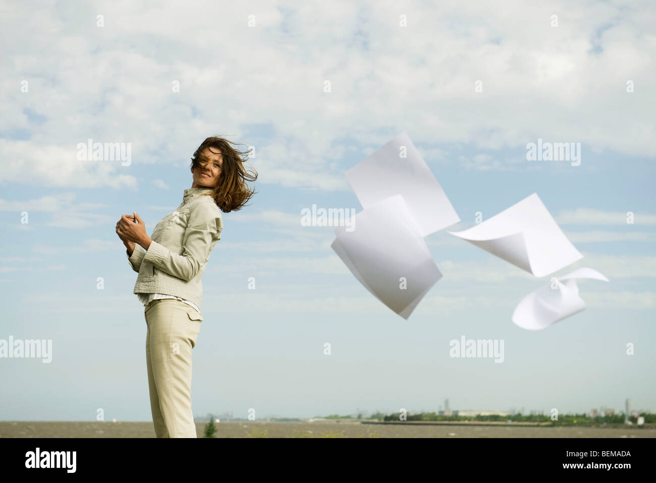 Woman outdoors smiling, watching documents caught in wind fly away - Stock Image