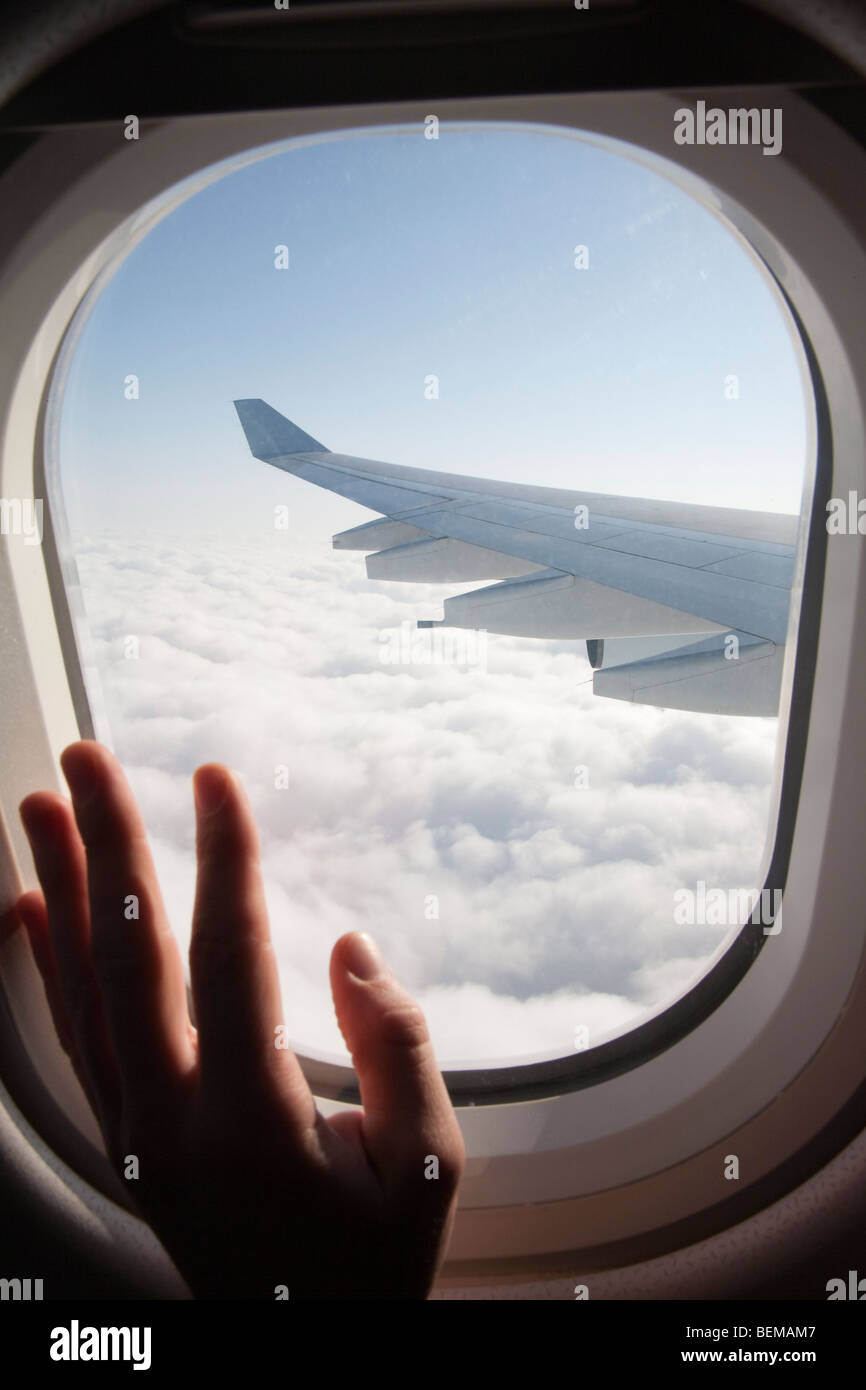 A passenger's hand on an airplane window. The airplane is Airbus A340, operated by Cathay Pacific airline. - Stock Image