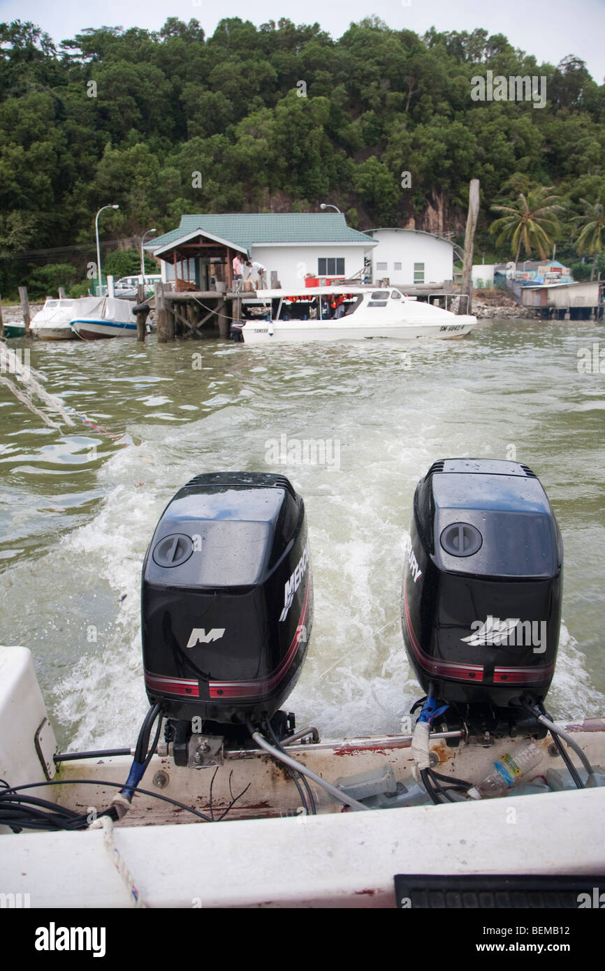 Boat with two outboard motors leaving a dock. - Stock Image