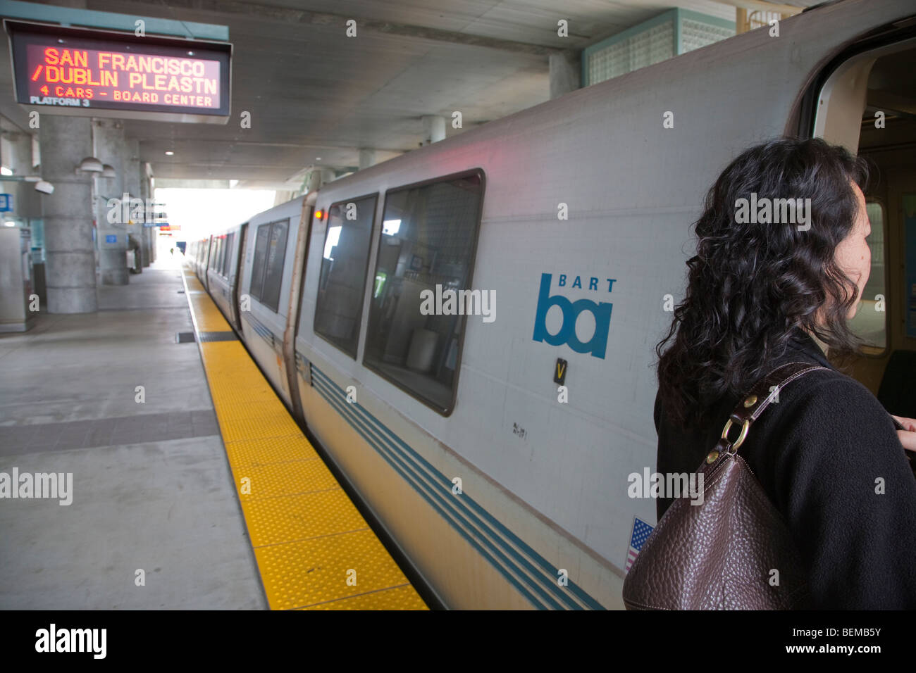 A woman boarding a commuter train at BART station. Millbrae, California, USA - Stock Image