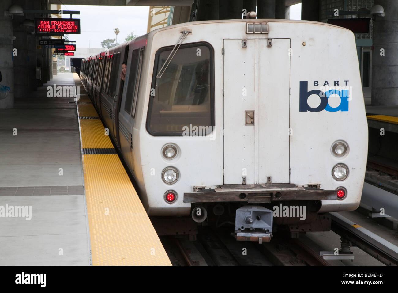 A BART heavy rail train arriving at station. Millbrae, California, USA - Stock Image