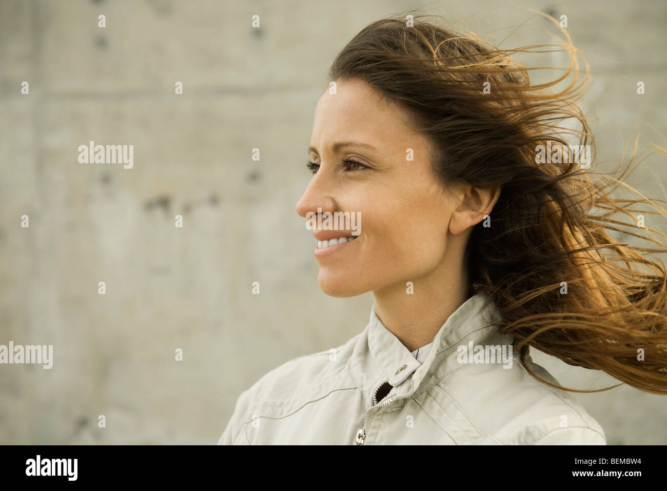 Woman looking away, hair tousled by breeze, portrait - Stock Image