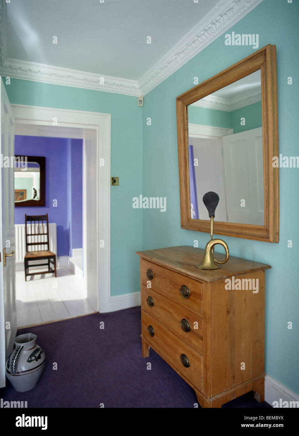 Mirror Above Chest Of Drawers On Turquoise Landing With Door Open Into Blue  Bathroom